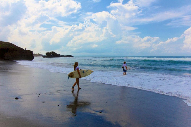 Featured image for 15-day relax pack yoga retreat in Pelan Pelan Bali with two surfers heading in to Balinese ocean to surf