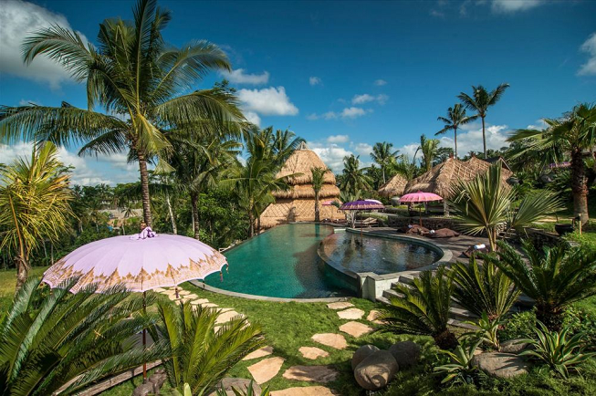 Featured image for 4-day intensive yoga retreat in Ubud, Bali with breathtaking image of Blue Karma Retreat Resort showing poolside view, bamboo built structures, a pink umbrella, lush green landscape and more