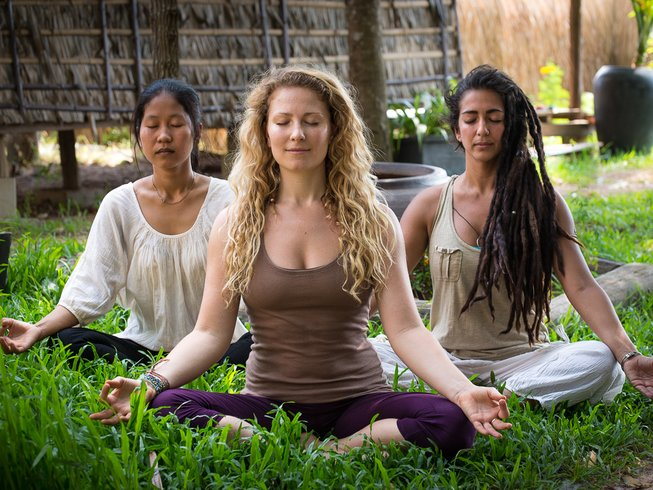Featured image for Top 30 Yoga Retreats for November, 2017 Holiday Season with 3 female yogis in lotus pose, meditating outside on green grass at the 6-Day Integral Yoga and Meditation Retreat in Cambodia