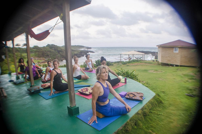 Featured image of top 30 yoga retreats for November 2017 with an outdoor female yogi class in middle of pose and the beautiful Long Bay, Jamaican ocean in the background for the 6 Day Juice Cleanse Detox, Yoga and Meditation Retreat in Long Bay, Portland Parish, Jamaica