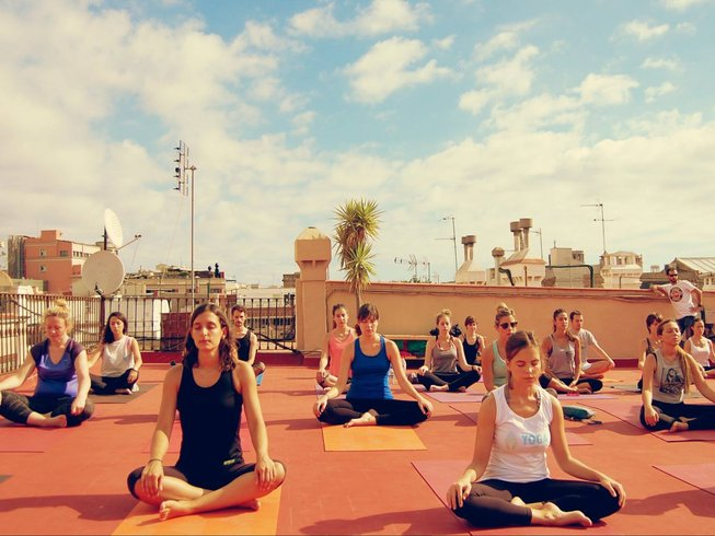 Featured image for Top 30 Yoga Retreats for November, 2017 Holiday Season with an outdoor class of yogis in lotus pose at the 6-Day Urban Yoga Retreat in Barcelona, Spain hosted by Yoga Weeks Barcelona