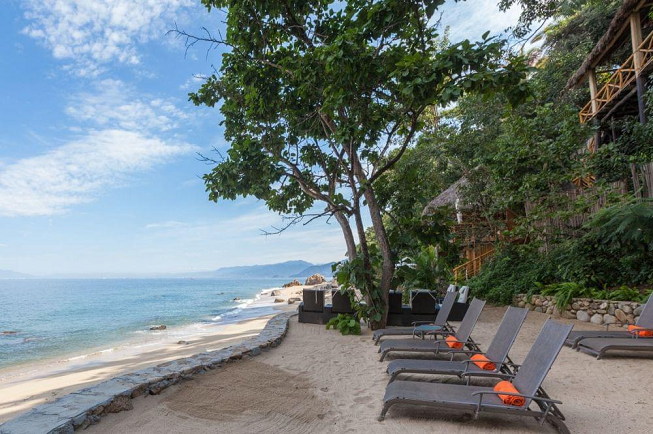 Featured image of top 30 yoga retreats for November 2017 with 7-Day Exclusive Yoga Retreat in Puerto Vallarta, Mexico displaying beachside view with patio chairs and a crystal clear blue sky