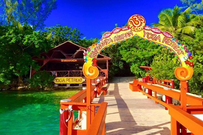 Featured image of top 30 yoga retreats for November 2017 with 8-Day Sivananda Yoga and Meditation Holiday Retreat in the Bahamas displaying crystal clear green water with royal blue sky and a deck with orange rails and an arch shaped welcome sign reading Sivananda Ashram Yoga Retreat