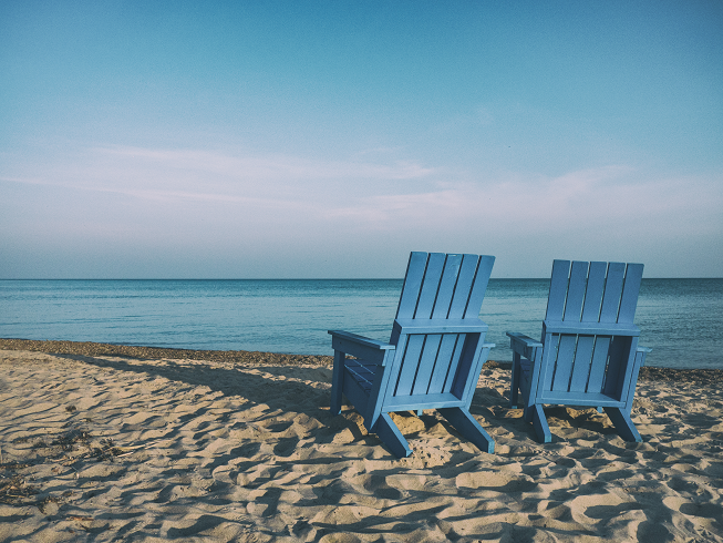 Featured image for two 4-day budget yoga retreats for 2017 in Bali, Indonesia with two blue beach chairs on sand by Bali beach