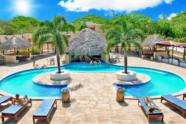 Featured image of top 30 yoga retreats for November 2017 with 6-day yoga and surf retreat in Nicaragua displaying view of the resort with shiny blue water pools, palm trees, bamboo cabanas and stone walkway