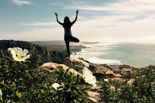 Featured image for 7-day yogi adventure retreat in Lisbon, Portugal with female yogi doing stadning one-legged yoga pose overlooking the lovely ocean