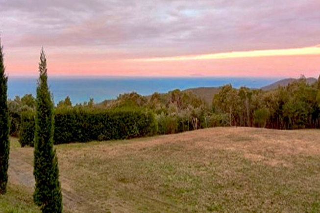 Featured image for 8-day transformation yoga retreat in Tuscany, Italy with a picture-perfect sunset colored in peach, orange, pink and light purple above an ocean blue water setting