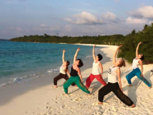 Featured image for 8 Days Yoga Retreat in Maldives with female yogis in pose at white sandy beach of Maldives island
