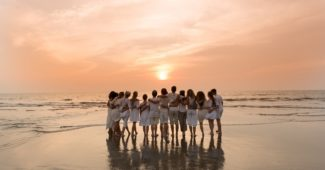 Yin yoga teacher training sunset pic at beach in Goa, India with trainees hugging